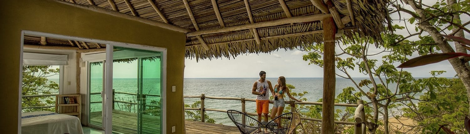 Young couple on hotel room balcony in View of Flamingos from the beach in Riviera Nayarit Mexico