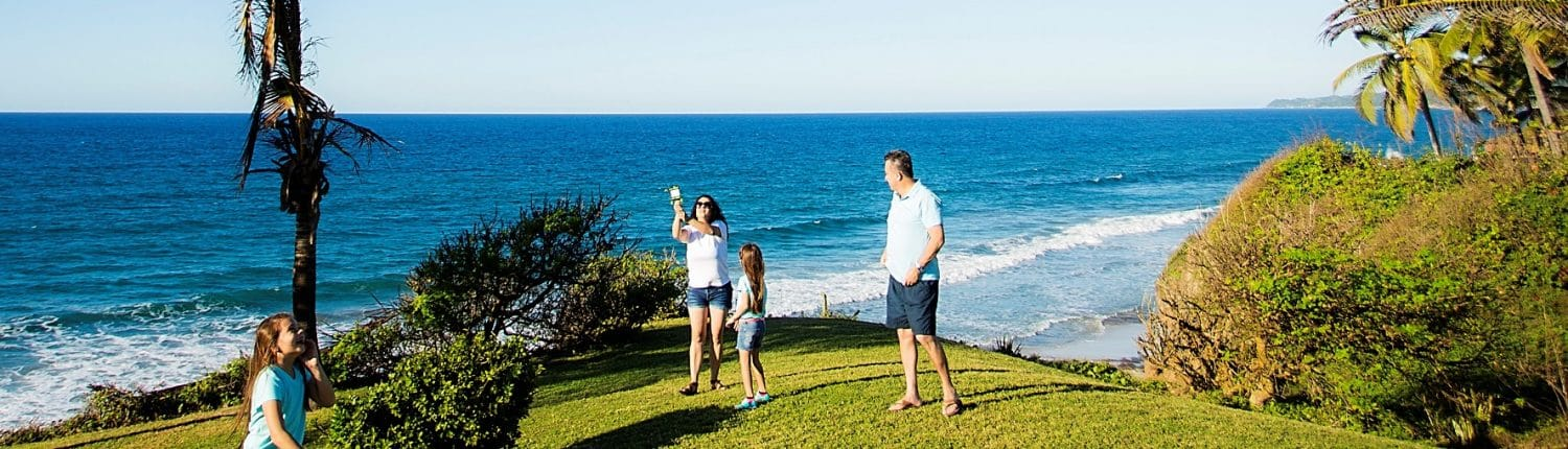 Why Invest in Riviera Nayarit Mexico - image of Family of 4 playing on lawn by the ocean