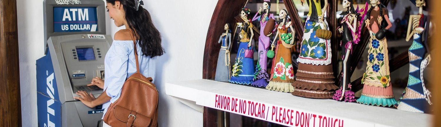 Local services in Riviera Nayarit - Woman at ATM machine beside Day of the Dead window display