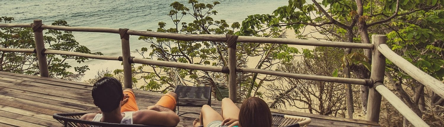 Moving to Riviera Nayarit Mexico - image of couple sitting on balcony overlooking the beach