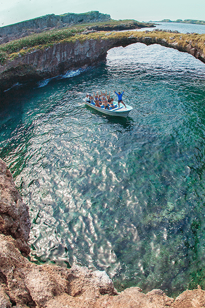 Group of people in a boat inside Marietas with natural bridge behind them