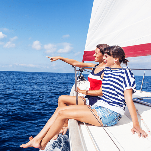 Two woman sitting on the edge of a boat pointing at something