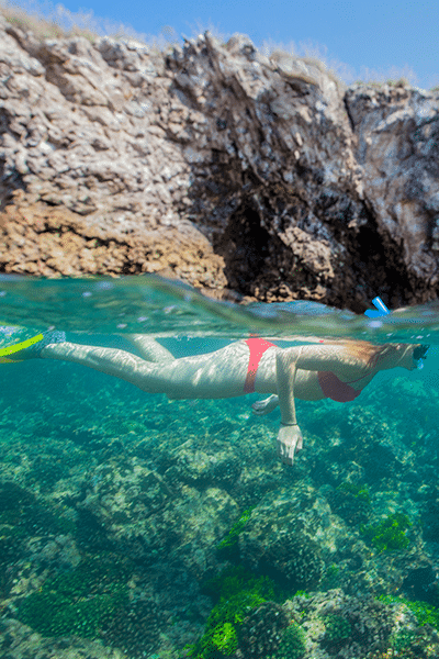 Young woman snorkelling in clear water next to shore