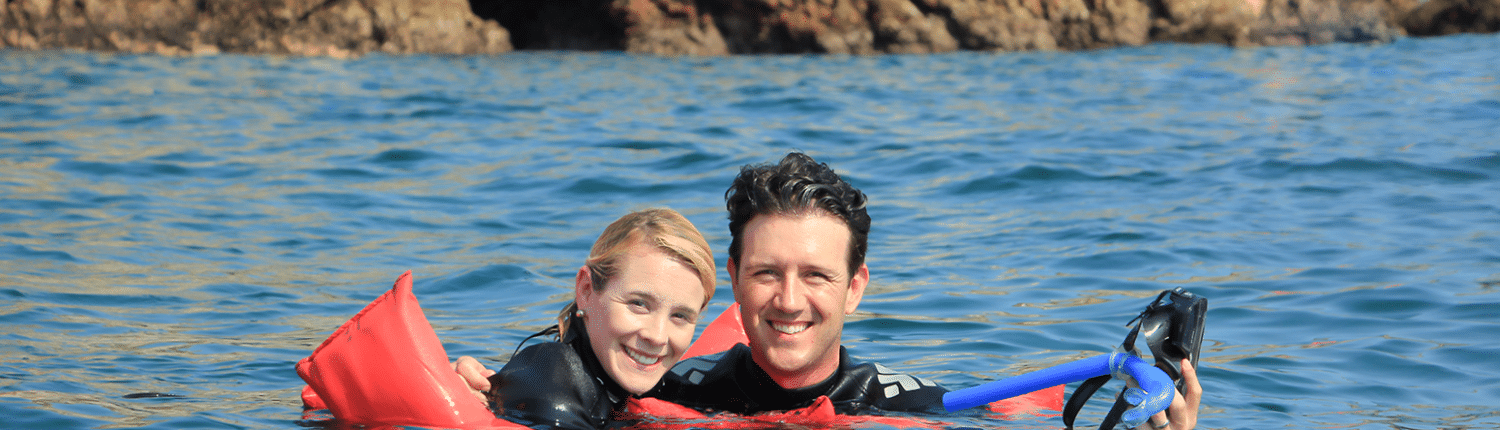 Young smiling couple in the water with snorkelling gear