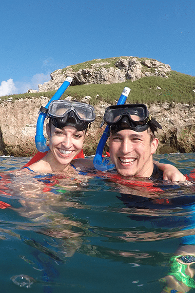 Young couple in snorkelling gear posing for a photo