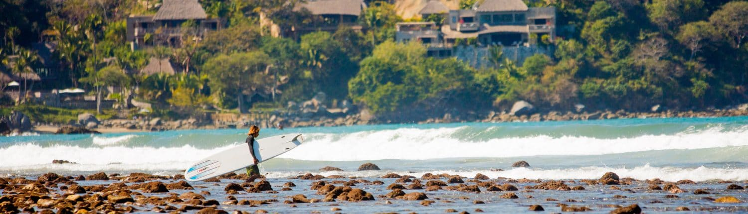 Surfer with board heading into the water in Riviera Nayarit Mexico