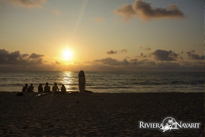 Surfers sitting on the beach at Sunset in San Pancho Riviera Nayarit Mexico