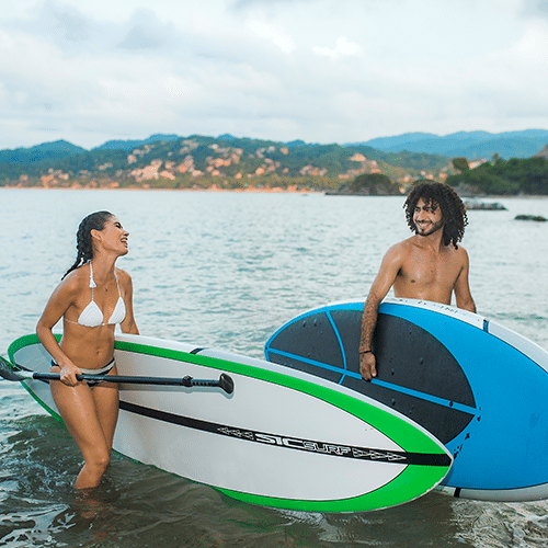 Young couple coming ashore with their paddle boards in Riviera Nayarit MX