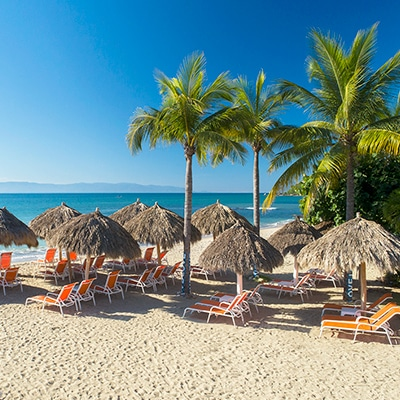 Sandy beach with lounge chairs and shade at Grand Matlali Hills Resort & Spa