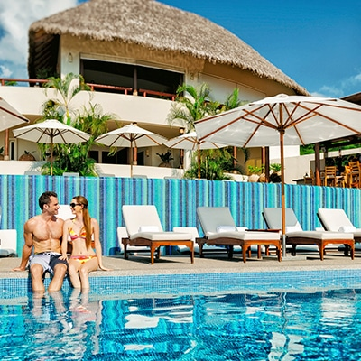 Young couple sitting at the pool at Grand Matlali Hills Resort & Spa