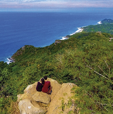 Young couple on a rocky hilltop with a view of the Pacific Ocean in Riviera Nayarit MX